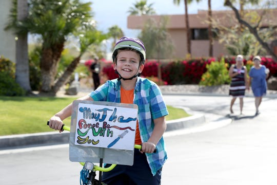 A child rides his bike inside Belmonte Estates in Palm Desert, Calif., as part of the organized neighborhood walk on Saturday, March 28, 2020 as a way to break up the isolation during the coronavirus pandemic.