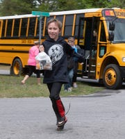 Spencer Woodcock is happy to receive a packed lunch from the Santa Rosa County School District from its delivery program on Monday, March 30, 2020. In the wake of school closure associated with the COVID-19 outbreak, the school district is using buses to deliver meals to students.