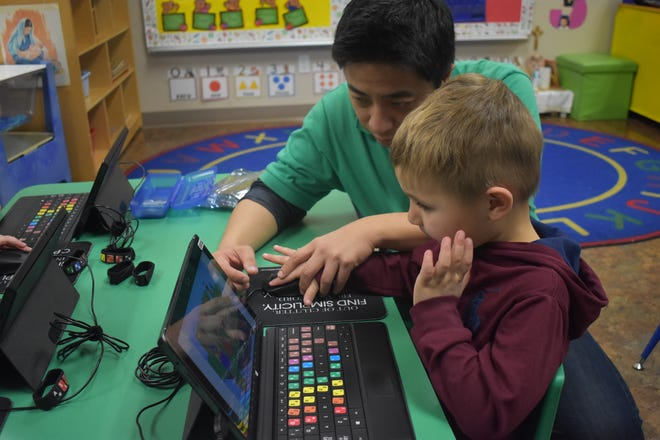 Future Kiddie's Ken Chan teaches Harrison Carroll, a student at St. Maria Goretti Preschool in Scottsdale, about finger positions on a computer keyboard.