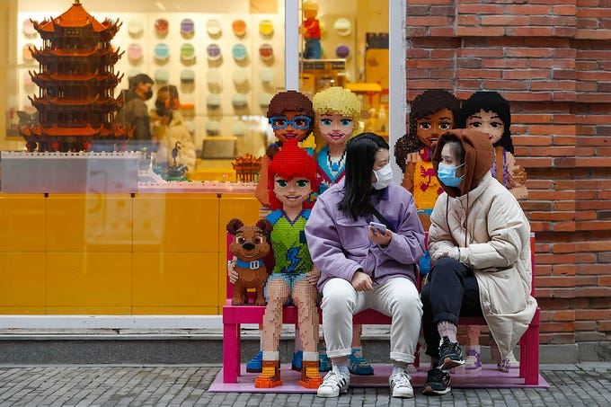 In this photo released by Xinhua News Agency, women wearing protective masks to prevent the new coronavirus outbreak chat with each other outside a Lego store at a re-opened commercial street in Wuhan in central China's Hubei province on Monday, March 30, 2020. Shopkeepers in the city at the center of China's virus outbreak were reopening Monday but customers were scarce after authorities lifted more of the anti-virus controls that kept tens of millions of people at home for two months.