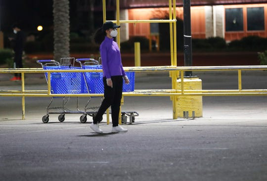 A woman wears gloves and a mask while grocery shopping in Mesa, Ariz. March 29, 2020. Shoppers have been using masks and gloves to protect themselves from COVID-19.