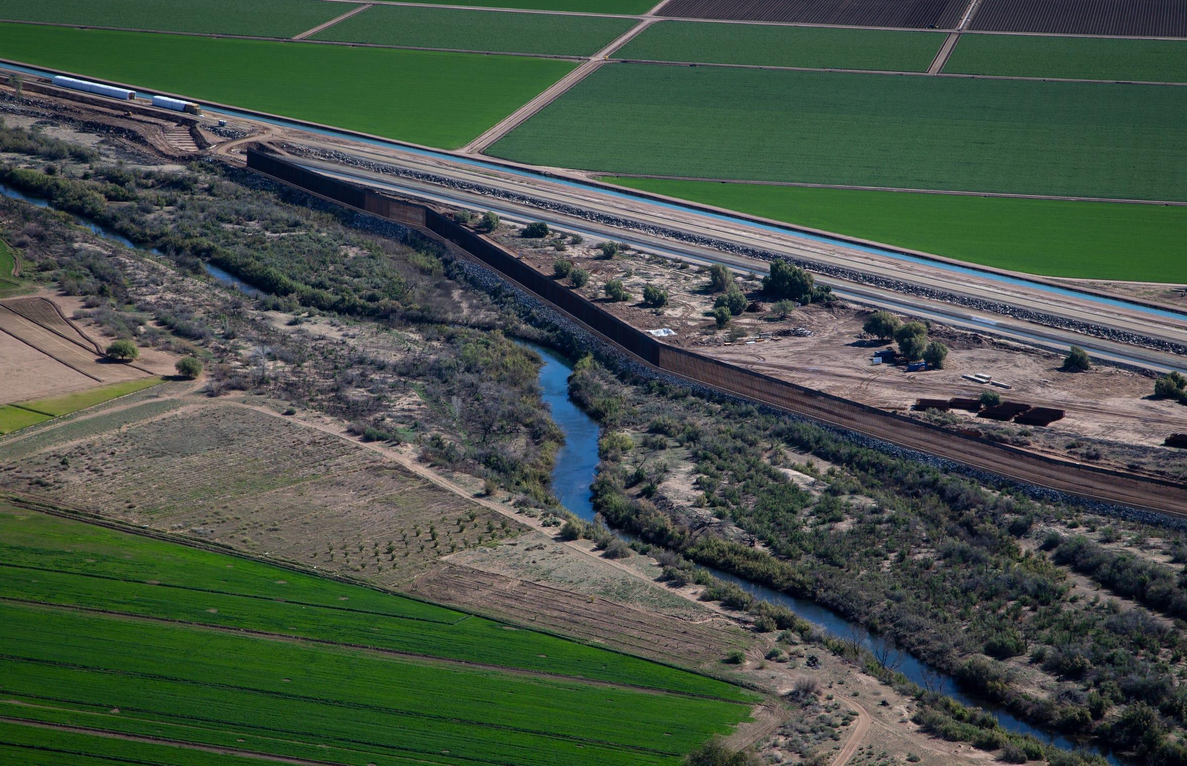 El Río Colorado fluye junto al muro fronterizo al sur de la presa Morelos en México.