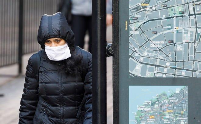 Una mujer con una máscara camina por Wall Street, cerca de la Bolsa de Nueva York en Nueva York, Nueva York.