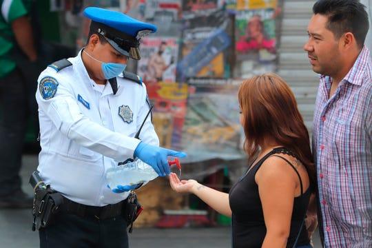 Policías de la secretaria de seguridad pública, aplican gel a personas caminan este domingo, en una de las principales avenidas, en Ciudad de México (México).