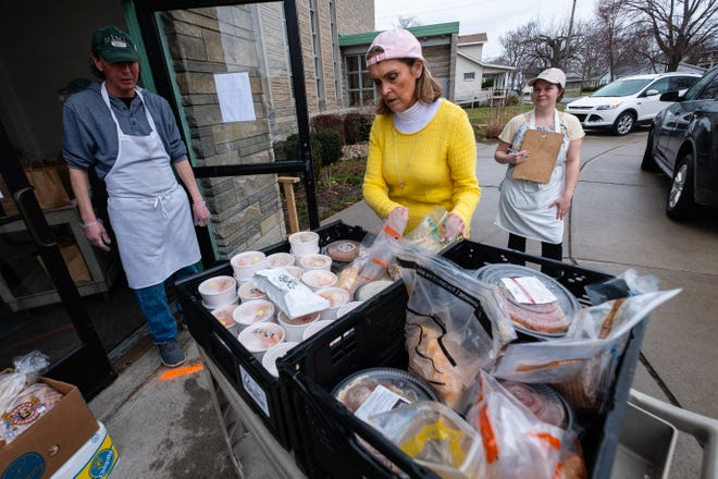 Mid City Nutrition Executive Director Alice Rieves, center, looks over packaged meals Monday, March 30, 2020. outside St. Martin Lutheran Church. The kitchen's volunteers were handing out about 200 meals a day, according to Rieves.