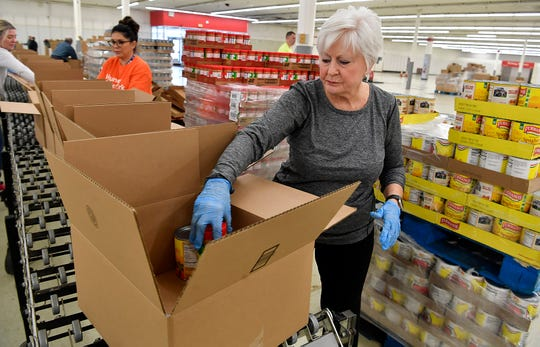 Volunteer Cheryl Abel of Springettsbury Township puts pasta sauce in a food box at the York County Food Bank's new East York Food Hub in preparation for distribution, Monday, March 30, 2020. The new food hub is located in the former Kmart location, 1094 Haines Road in Springettsbury TownshipJohn A. Pavoncello photo