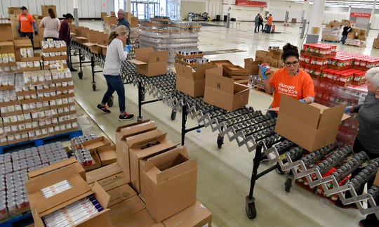 Volunteers box food at the York County Food Bank's new East York Food Hub in preparation for distribution, Monday, March 30, 2020. The new food hub is located in the former Kmart location, 1094 Haines Road in Springettsbury TownshipJohn A. Pavoncello photo