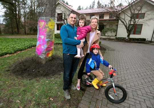 Sonjay and Ally Hiranandani with their children Arjun, 4, and Sonya, 16 months, in front of a tree they decorated to show their support during coronavirus isolation. Several families in their Brighton neighborhood decorated their trees.