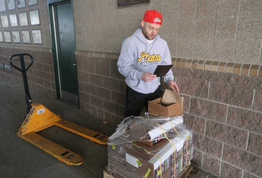 Rochester Red Wings Promotions Manager Tim Doohan checks the magnetic season schedules that just arrived.  He had to come to the stadium to take delivery of the shipment since the building is closed because of the coronavirus outbreak.