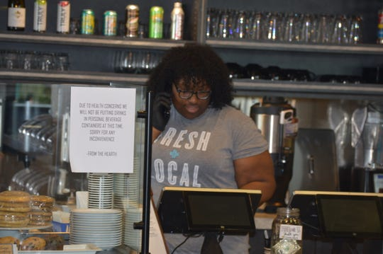 From the Hearth Cafe barista Aristomelia Vidal takes phone calls from customers on March 30, 2020.