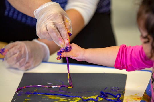 Wearing gloves, Fabiloa Ramirez helps a child finger paint at the East Lancaster Community Center in Salem on March 30, 2020. The program, usually for pre-school aged children, has extended their age range up to 12 years old.