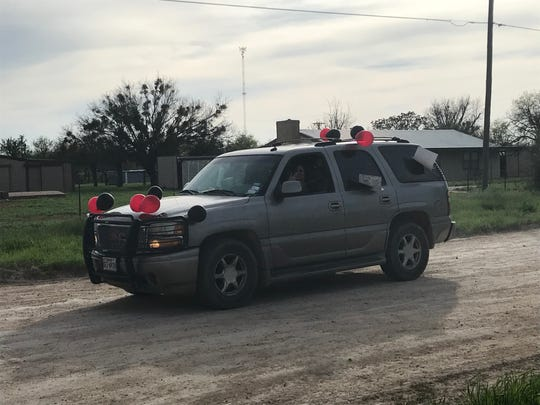 A Ballinger ISD teacher drives down a dirt road as part of a parade through town involving teachers, coaches and administrators Monday, March 30, 2020, due to students now missing a third straight week of scheduled classes because of the coronavirus pandemic.