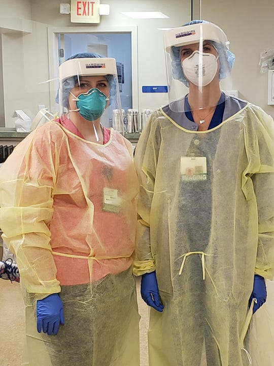 Two healthcare workers at Atlantic General Hospital test Hardwire LLC's new face shield during product testing before the company begins producing the protective equipment in large quantities.