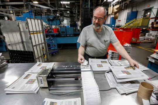 Mike Lillie attaches mailing labels onto papers during the final press run on the Springfield News-Leader's press on Sunday, March 29, 2020. Printing operations for the News-Leader have been moved to Columbia, Mo.