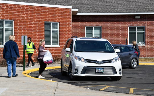 STRIDE Academy staff members distribute packets of school work and other items to student's families Monday, March 30, 2020, in St. Cloud.