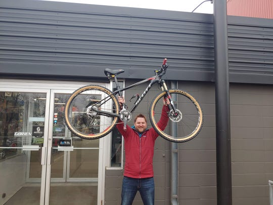 Andrew Scully holds up the bike returned to him in March 2020, six years after it was stolen. Fitzharris Ski, Bike & Outdoor co-owner Mike Rathlisberger found it in an online sale post.
