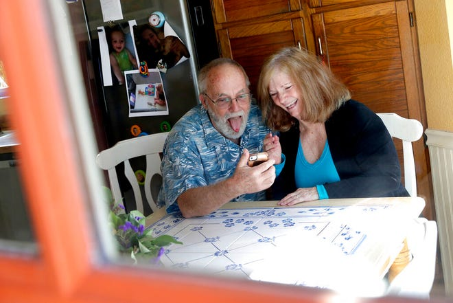 Seen through their kitchen window, Allan and Debbie Cameron contact their grandchildren via the internet Wednesday, March 25, 2020, in Chandler, Ariz. Debbie, 68, has asthma which makes her one of the people most at risk from the new coronavirus. The Cameron's now she see their children and grandchildren from the other side of a window or a phone. (AP Photo/Matt York)