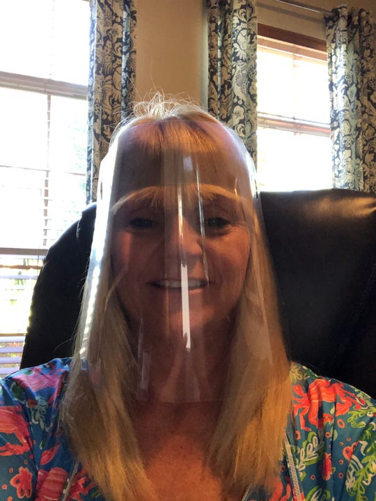 Sherry Hendricks, of Vero Beach, wearing the face shield produced by a company, which recently donated 1,000 of the items to local fire departments.