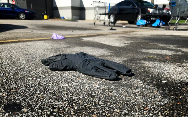 Various types of gloves litter the parking lot of the Walmart on Okeechobee Road Monday, March 30, 2020 in Fort Pierce. Some shoppers have been using gloves while shopping inside stores and discarding them after loading their vehicles.