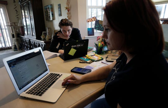 Christina Sordini, foreground, a teacher at Tom Lea Elementary School, prepares lessons as her son, Nicholas Sordini, a Parkland Early College High School student, works on an assignment Monday, March 30, 2020, on the first day of distance learning due to the coronavirus closure.
