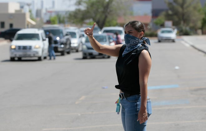 Miriam Carlos keeps the line straight at the El Pasoans Fighting Hunger Food Bank Monday as the line stretched for nearly a half mile.