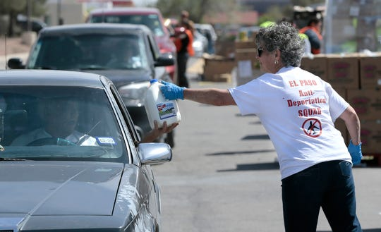 Volunteers hand out mild to those in line at the El Pasoans Fighting Hunger Food Bank Monday.