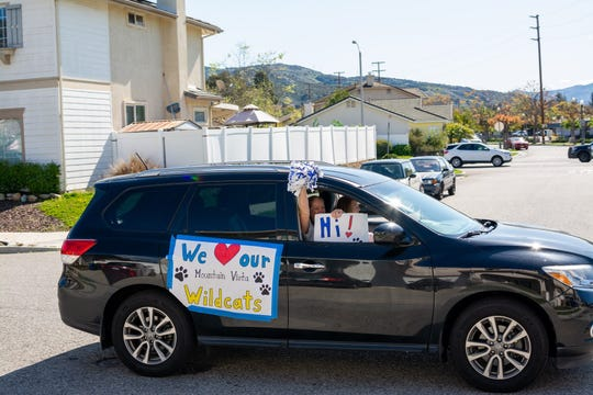 A Mountain Vista School teacher waves a pom pom out of a moving car as part of a social distancing parade in Fillmore.