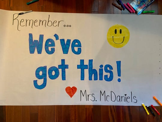 Mountain Vista School Principal Christine McDaniels makes a sign for the social distancing parade to send a message to students.
