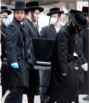 People carry the casket of Josef Neumann during his funeral at Viznitz Cemetery in Spring Valley March 30, 2020. Neumann, 72, died from his injuries suffered in the Monsey Hanukkah machete attack.
