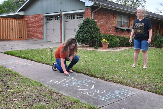 Julie Woolsey watches as her daughter, Haley Woolsey, adds to one of the many messages written with sidewalk chalk to encourage people walking through the neighborhood.
