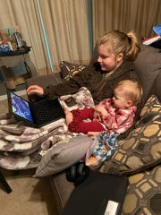 London Johnston, 14, works on School@Home Monday while sitting with her youngest sister, nearly 1-year-old Charlotte Johnston. London is an eighth-grader at McNiel Middle School, and the two girls are the daughters of Lara and Patrick Johnston.