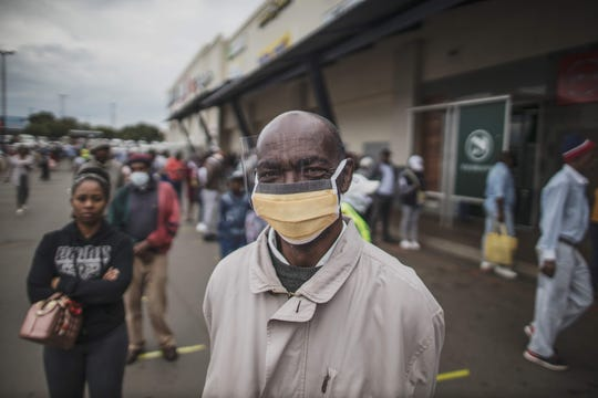 An elderly man from Soweto wears a mask while lining up  at a SASSA (South African Social Security Agency) pay-point in Soweto on March 30, 2020. South Africa came under a nationwide lockdown on March 27, 2020, joining other African countries imposing strict curfews and shutdowns in an attempt to halt the spread of the COVID-19 coronavirus across the continent.