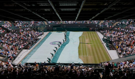 Ball boys take off the rain covers on No.1 Court, at the All England Lawn Tennis Championships in Wimbledon, London, Tuesday July 7, 2015.