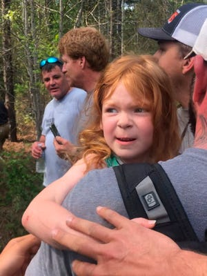 Rescuers carry 4-year-old Vadie Sides out of the woods in Lee County, Ala., after the girl was found with a dog at her side after two days in the woods.