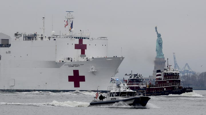 The U.S. Navy Hospital Ship Comfort makes its way past the Statue of Liberty as it sails into New York City March 30, 2020 to aid in the city's battle with the coronavirus. The ship will provide 1000 hospital beds to make room in city hospitals for COVID-19 patients.