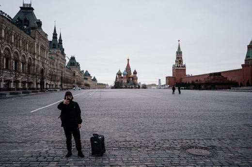 A tourist takes a selfie on the deserted Red square with the Saint Basil's Cathedral and Kremlin's Spasskaya Tower in the background on March 30, 2020 in Moscow as the city and its surrounding regions imposed lockdowns today, that were being followed by other Russian regions in a bid to slow the spread of the COVID-19 infection caused by the novel coronavirus. The enforcement of the strict new rules, which Moscow Mayor suddenly announced for the capital late Sunday, coincide with the beginning of a