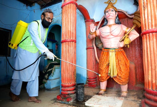 A volunteer disinfects a Hindu temple in an effort to contain the outbreak of the coronavirus, in Karachi, Pakistan, March 30, 2020.