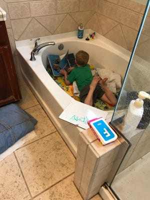 "Orion Carlson, age 4, learning phonics from his makeshift classroom ""tub"" at home in Alameda, California."
