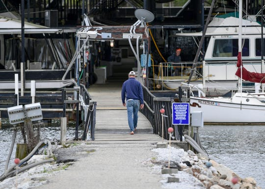 A boat repairman walks to one of the many houseboats docked at Portman Marina on Lake Hartwell in Anderson Tuesday.
