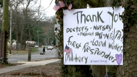 A sign hung on trees outside the Fischer's Princeton Avenue home in Brick Township Tuesday, March 31, 2020, shows their thanks to those on the front lines during the coronavirus pandemic.