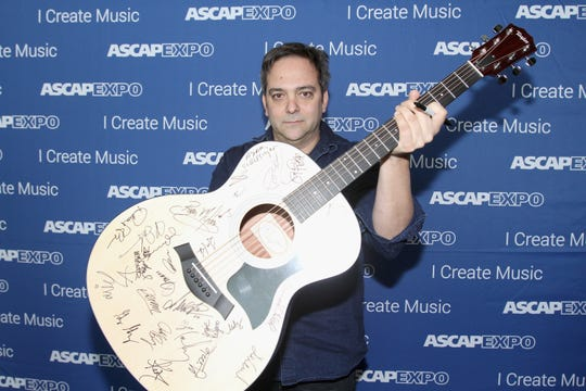 """Composer Adam Schlesinger poses with a #StandWithSongwriters guitar which will be presented in May to members of Congress to urge them to support reform of outdated music licensing laws, during the 2016 ASCAP """"I Create Music"""" EXPO on April 30, 2016 in Los Angeles, California."""