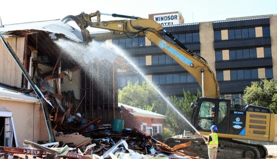 The jaws of demolition equipment close in on the roof of Civic Plaza Hotel on Tuesday. The downtown hotel is being torn down.