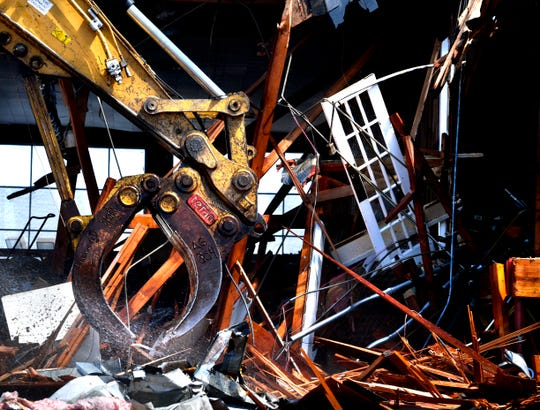 A mechanical claw pulls metal tubing and other material out of the piled rubble around Civic Plaza Hotel Tuesday as it was being torn down.