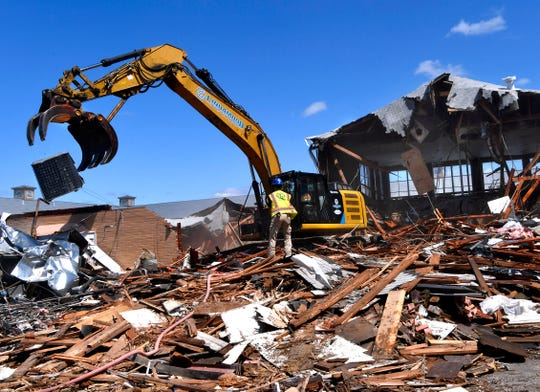 An air conditioning unit is dropped onto a pile of salvaged metal as the Civic Plaza Hotel is demolished Tuesday.