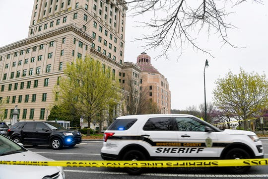 Law enforcement surround Buncombe County Courthouse and City Hall in downtown Asheville after shots were fired March 31, 2020. The suspect was killed in the altercation and a sheriff's office lieutenant sustained non-life threatening injuries.