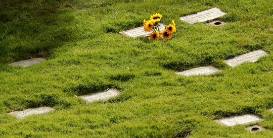 A bouquet of sunflowers adorns a headstone at Forest Lawn Cemetery in Bremerton on Tuesday.