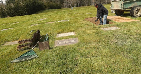 """Groundskeeper Javier Zatarain fills in a gravesite with soil at Forest Lawn Cemetery in Bremerton on Tuesday. Funerals, initially prohibited during Gov. Jay Inslee's """"Stay Home, Stay Healthy"""" order, are now allowed to go forward with """"immediate family"""" and """"no hugging."""""""