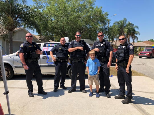 Hunter Hand stands with members of the Palm Bay and West Melbourne Police Department