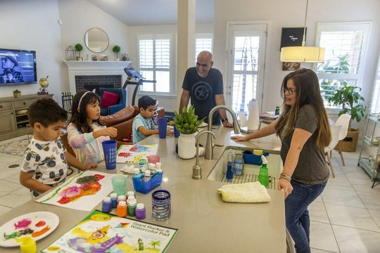 Bob and Martha Perez joke with their children Aiden and Alexia, both 7, and Alec, 3, as they paint in the kitchen Tuesday. Practicing social distancing has increased their family quality time.
