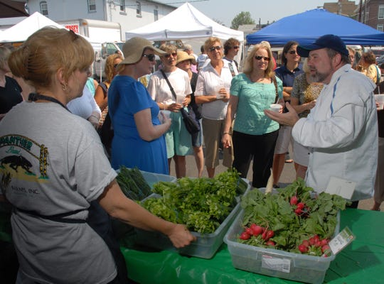 Chef Mark Smith , in white jacket, talks to his tour guests at Flaim Farm's tent in the the Collingswood Farmer's Market.